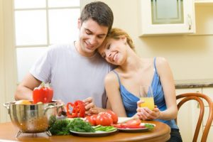 Young happy couple making salad at home together