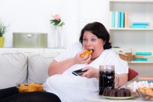 Dicke Frau mit Chips und Fernbedienung auf der Couch © fotolia Picture factory