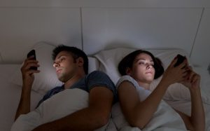 Young couple with smartphones in their bed